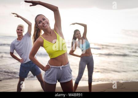 Gruppe von Menschen Übungen am Strand. Fitness, Training, Sport und Personen Konzept - Stockfoto