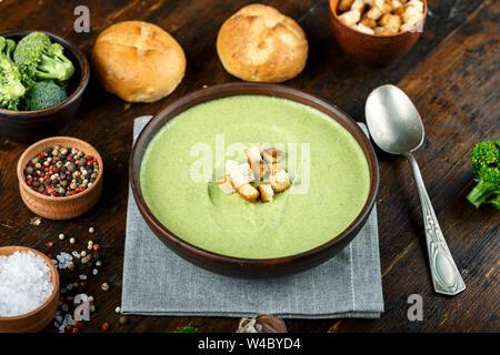 Grünes Gemüse Cremesuppe von Brokkoli in eine Platte auf einem hölzernen Hintergrund. In der Nähe sind Brötchen und Gemüse - Stockfoto