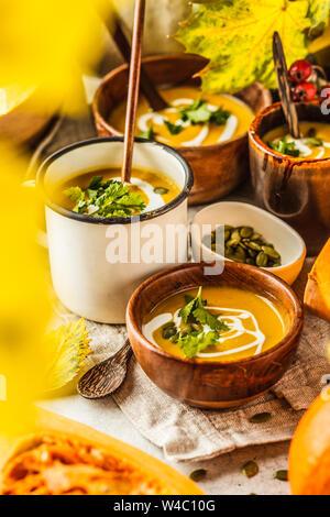 Herbst Kürbis Suppe pürieren, mit Sahne in cups, dem Herbst Landschaft. Gesunde vegane Ernährung Konzept. Herbst essen Konzept. - Stockfoto