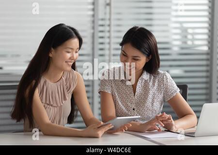 Lächelnd asiatischen Mentor helfen Kollegen intern Client mit digitalen Tablet - Stockfoto