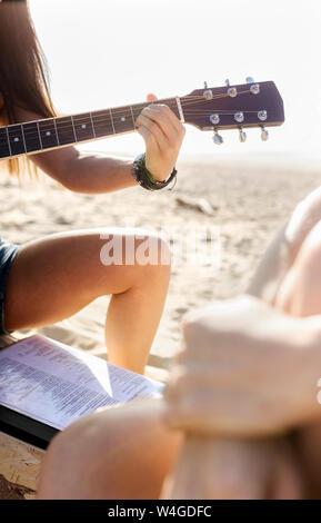 In der Nähe von Frau Gitarre spielen am Strand Stockfoto