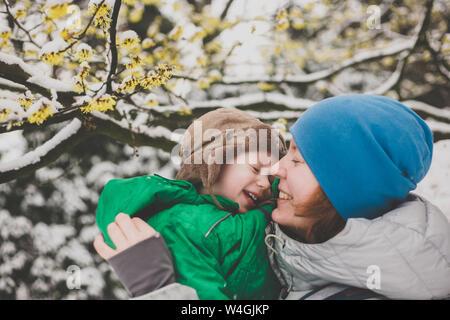 Mutter mit ihrem kleinen Sohn unter Schnee - unter eine Hexe abgedeckt - hazel Tree - Stockfoto