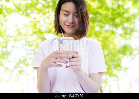 Entspannt Frau mit Handy und Kopfhörer bei einem Picknick im Park - Stockfoto