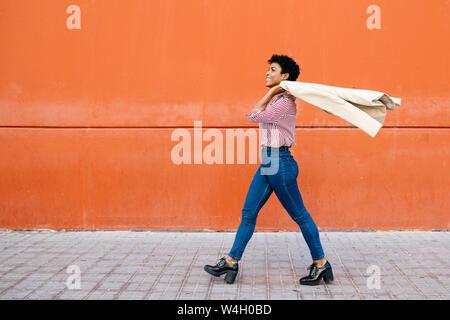Geschäftsfrau zu Fuß an der Roten Wand im Hintergrund, die ihre Jacke auf ihrer Schulter Stockfoto
