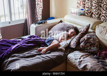 Kleiner Junge schlafend auf dem Bett couch am Morgen Stockfoto