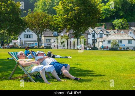 Hafen von Lynmouth, North Devon, England. Dienstag, den 23. Juli 2019. UK Wetter. Mit steigenden Temperaturen unter blauem Himmel, Urlauber genießen genießen Sie die Sonne im Kleinen Park neben dem malerischen Hafen von Lynmouth in North Devon. Credit: Terry Mathews/Alamy leben Nachrichten