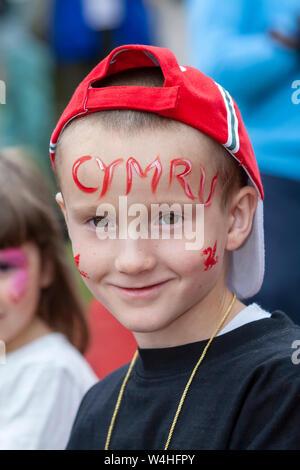 """Portrait einer jungen Waliser Junge mit Baseball Cap auf Rückwärts und Gesicht gemalt mit dem Wort """"Cymru"""" - Stockfoto"""