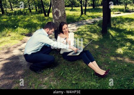 Young Business Paar an einem Projekt arbeitet unter dem Baum in einem öffentlichen Park selektiven Fokus - Stockfoto