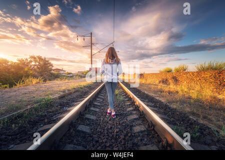 Stehende junge Frau auf die Eisenbahn bei Sonnenuntergang im Sommer - Stockfoto