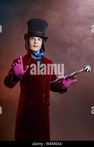 Fabelhafte Zirkus Mann in einem Hut und einem roten Anzug posiert in der Rauch auf einem farbigen dunklen Hintergrund. Ein Clown auf einer Party, Mann Herr aus einem Märchen. Wiz - Stockfoto