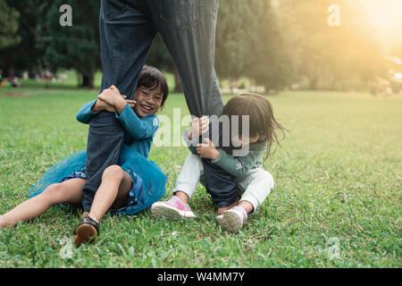 Zwei kleine Tochter gemeinsam Spaß mit ihrem Vater. - Stockfoto