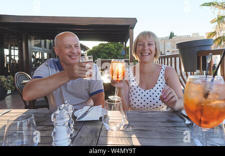 Im mittleren Alter paar Baby boomers Menschen lächeln und genießen mit Getränken im Restaurant auf sonnigen Sommer Abend - Stockfoto