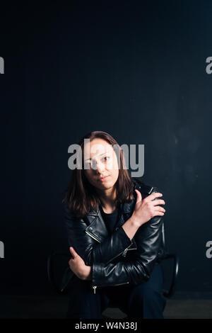 Studio Portrait einer attraktiven jungen Frau in schwarzem Leder Jacke gegen einen einfachen Hintergrund Stockfoto