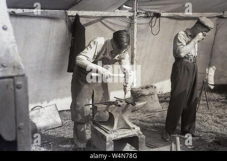 """1950, historische, ein hufschmied auf ein Hufeisen mit einem Hammer und einem Amboss in einem Zelt außerhalb der Arbeit für einen Country Fair, England, UK. Traditionell die Arbeitsplätze von einem Schmied und einem Schmied waren die gleichen, mit dem Wort """"hufschmied"""", die sich aus dem französischen Wort für Schmied (ferrier). - Stockfoto"""