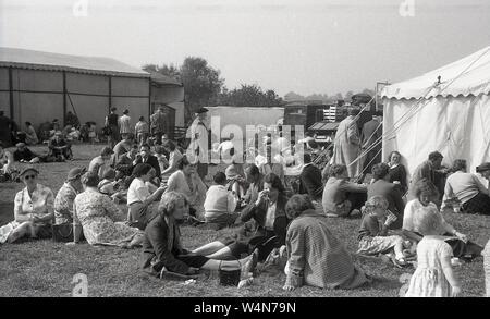 1950, historische, an einem Englisch Country Fair, Besucher entspannen auf dem Gras außerhalb ein Zelt, England, UK. - Stockfoto