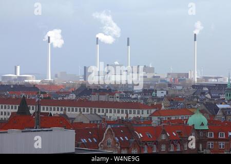 Industrie in Dänemark. Blick über Kopenhagen mit der ganzen Stadt im Schatten und Sonne über Industrial Area - das Kraftwerk. - Stockfoto