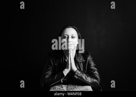 Studio Portrait einer attraktiven jungen Frau in schwarzem Leder Jacke gegen einen einfachen Hintergrund - Stockfoto