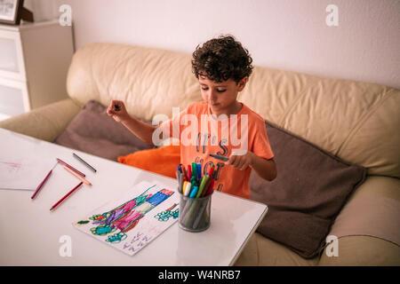 Curly - behaartes Kind ist an einem Tisch Malerei Zeichnungen mit Farben Stockfoto