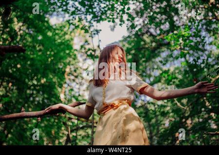 Frau, die auf einem Baum in einem gelben Kleid Stockfoto