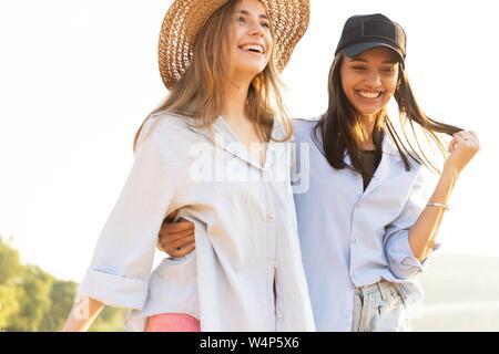 Zwei schöne junge Frauen bei einem Spaziergang am Strand. Weibliche Freunde zu Fuß am Strand und Lachen an einem Sommertag. - Stockfoto