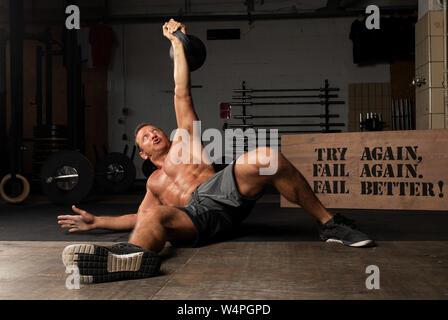 Eine athletische braungebrannte Mann mit robustem ABS tut Gewichtheben mit Ein kettlebell in ein Fitnessstudio. Übung Türkische aufstehen. - Stockfoto