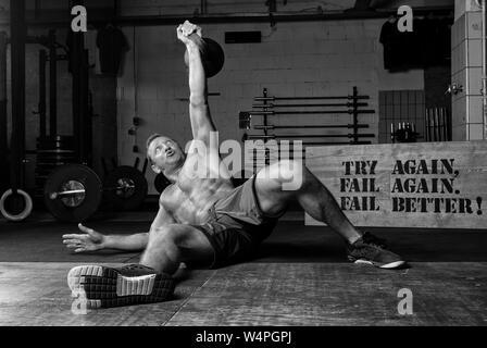 Eine athletische braungebrannte Mann mit robustem ABS tut Gewichtheben mit Ein kettlebell in ein Fitnessstudio. Übung Türkische aufstehen. Schwarz und Weiß. - Stockfoto