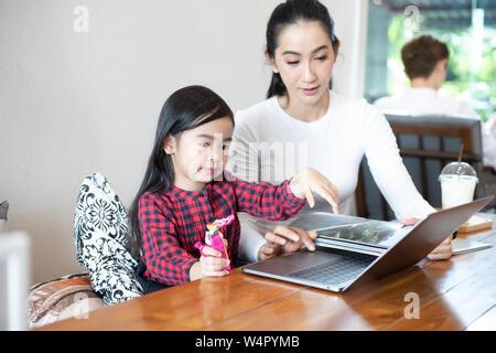 Mom ist die Lehre ihrer Tochter, ein Buch zu lesen und spielen Notebook. - Stockfoto