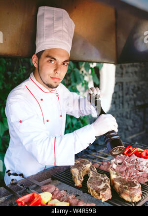 Der Küchenchef bereitet das Fleisch auf dem Grill. - Stockfoto
