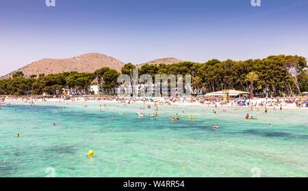 PLAYA DE MURO, SPANIEN - Juli 5, 2019: Touristen Sonnen und Schwimmen am Strand Muro am 5. Juli 2019 in Playa de Muro, Spanien. - Stockfoto
