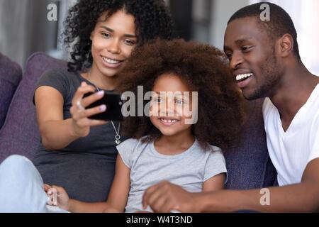 Fröhlich afrikanische Familie mit Kind nehmen selfie Foto mit Telefon - Stockfoto