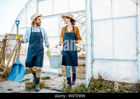 Zwei gut gekleideten Bauern oder Agronomen wandern Arbeiten mit Werkzeugen auf dem Ackerland in der Nähe von Das Treibhaus am Abend bei Sonnenuntergang - Stockfoto
