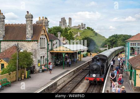 Corfe Castle, Großbritannien - Juli 8th, 2017: Eine restaurierte Dampfeisenbahn auf dem Bahnhof in Dorf von Corfe Castle in Dorset, Großbritannien anreisen. - Stockfoto