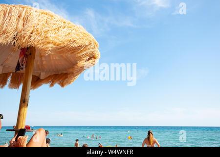 Strand schöne strohgedeckten Sonnenschirmen und leuchtend türkisfarbene Meer, tolle Erholung und Entspannung. - Stockfoto