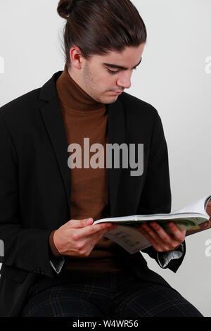 Jungen gutaussehenden Mann Lesen einer Zeitschrift. - Stockfoto