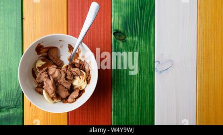 Blick von oben auf die Schokolade Eis mit Banane schneiden in eine Schüssel geben und mit einem Löffel. Über wooden Hintergrund. - Stockfoto