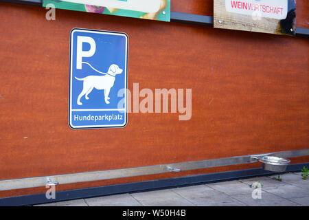 'Dog Parkplatz Station' für Hunde warten auf Besitzer außerhalb der Läden mit blauen Schild mit Hund an der Leine, Haken zum Befestigen von Leine und bewässerungskugeln - Stockfoto