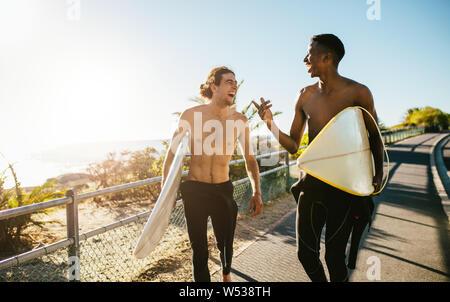 Lächelnd männliche Freunde zu Fuß in Richtung Strand mit Surfboards. Beste Freunde gehen auf das Surfen im Urlaub. - Stockfoto