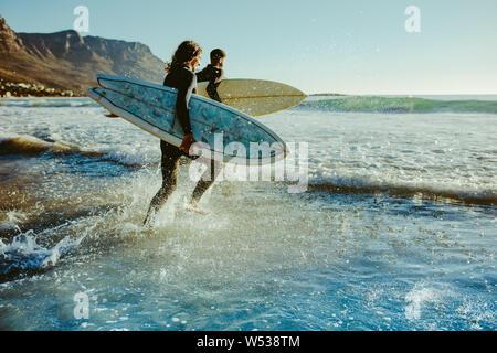 Zwei männliche Surfer gehen für Surfen im Meer. Zwei Männer, die surfbretter in zum Meer laufen für Surfen. - Stockfoto