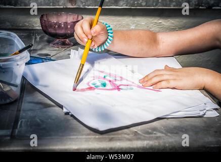 Eine Nahaufnahme von einem Mädchen, das Malen mit Aquarellfarben auf natürliches Licht - Stockfoto