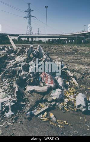 Stapel der illegalen gedumpten Müll in der Stadt Industriegebiet auf dem Hintergrund von Hochspannungsleitungen Stockfoto