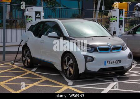 Aufladen des elektrischen Auto auf der Autobahn mit ökologisch erzeugtem Strom für das billige Öl Fahrt, die nicht die Welt kosten - Stockfoto