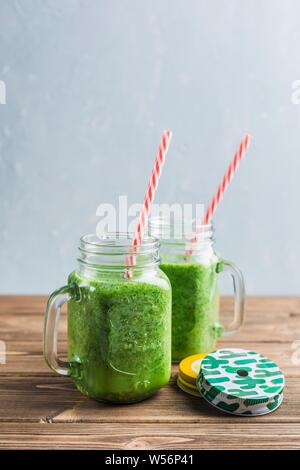 Grüne Smoothie mit Spinat, Apfel, Gurke und Kokosmilch auf Holz- Hintergrund. Der Blick von der Seite. Vegetarische trinken. Gesunde Ernährung. - Stockfoto