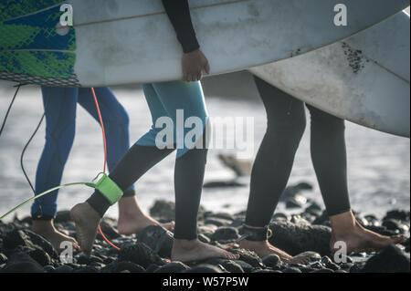 Nahaufnahme von drei Surfer am Strand mit Board barfuß gehen. Nahaufnahme der junge Beine der sportliche Männer am Strand. Gruppe von Jungen p