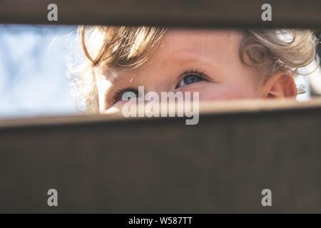 Baby blaue Augen Nahaufnahme. Baby, Kind, Sicht, die Konzentration, die Gesundheit der Augen, Neugier Entdeckung und Erforschung Konzept. Bild Detail schöne Blonde cur