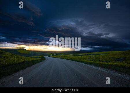 Dirt Road mit grünen Feldern und mit Blick auf den Sonnenuntergang mit schweren bewölkter Himmel - Stockfoto