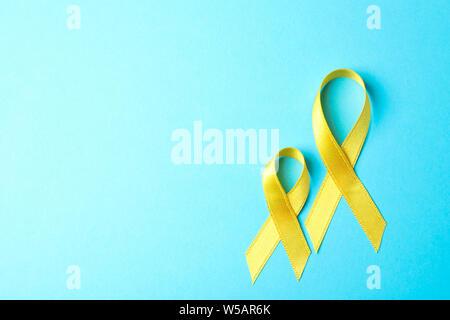 Gelbe Bewusstsein Bänder auf blauem Hintergrund, Platz für Text. - Stockfoto