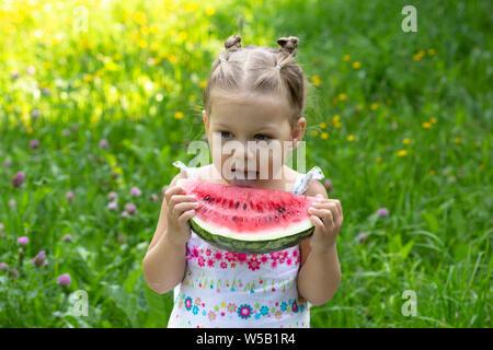Gerne kleine Mädchen, Essen, Wassermelone im Sommer Park - Stockfoto