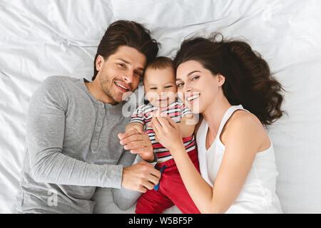 Junge tausendjährigen Eltern mit Baby Sohn im Bett - Stockfoto