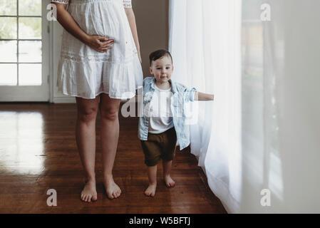 Kleinkind junge Hände mit schwangere junge Mutter - Stockfoto