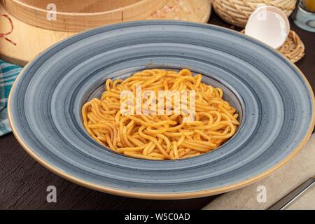 Spaghetti mit Bolognese Sauce in der Schüssel mit Tomaten, Rosmarin und Gewürzen. Auf schwarzem Hintergrund im Landhausstil - Stockfoto